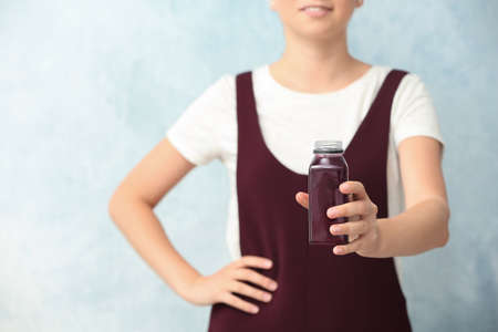 Woman with bottle of beet smoothie on light background, closeup Imagens