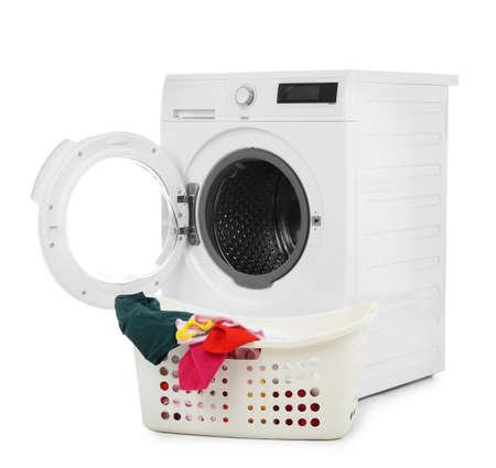 Modern washing machine and basket with laundry on white background
