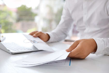 Male notary with documents and laptop at table in office, closeup Stock Photo