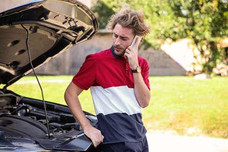 Young man talking on phone near broken car, outdoors Reklamní fotografie
