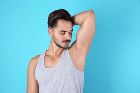 Handsome young man showing armpit on color background. Using deodorant Stock Photo