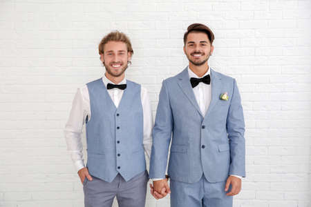 Happy newlywed couple in suits against white wall Stock Photo