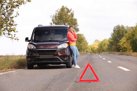 Emergency stop sign and driver near broken car on road. Auto insurance Stockfoto