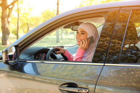 Muslim woman talking on phone in driver's seat of car