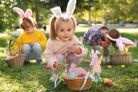 Cute little children hunting eggs in park. Easter tradition Stock Photo - 111793619