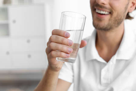 Young man holding glass of clean water indoors, closeup. Space for text