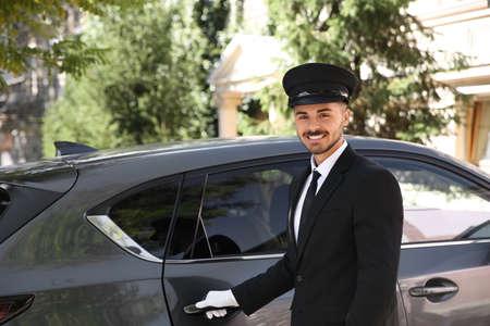 Jeune beau conducteur debout près d'une voiture de luxe. Service de chauffeur Banque d'images