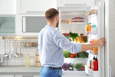 Man choosing food from refrigerator in kitchen