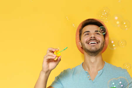 Young man blowing soap bubbles on color background. Space for text