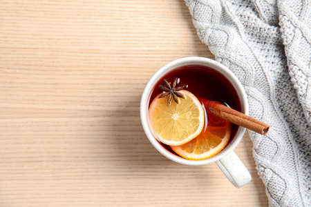 Hot winter drink in cup and warm sweater on wooden background, top view with space for text. Cozy season Stock Photo