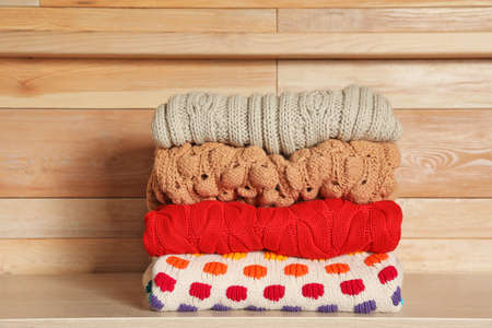 Stack of winter clothes against wooden background