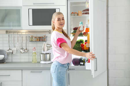 Woman taking products out of refrigerator in kitchen Фото со стока