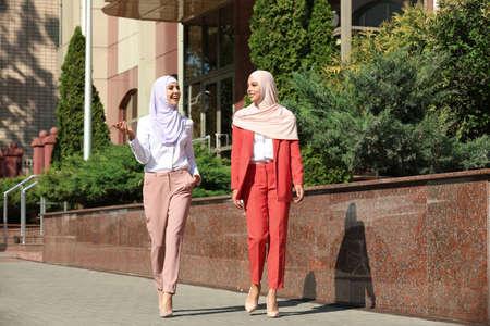 Muslim women in hijabs talking outdoors on sunny day 免版税图像