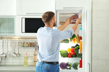 Man taking fresh meat out of refrigerator in kitchen