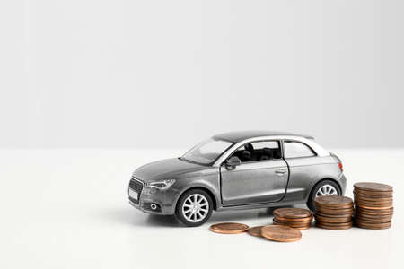 Toy car and money on white background, space for text. Vehicle insurance