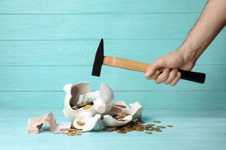 Man breaking piggy bank with hammer on table
