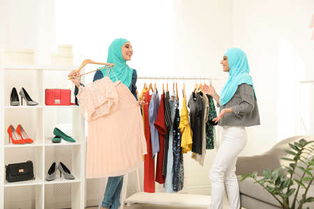 Muslim woman with her friend choosing clothes in modern shop