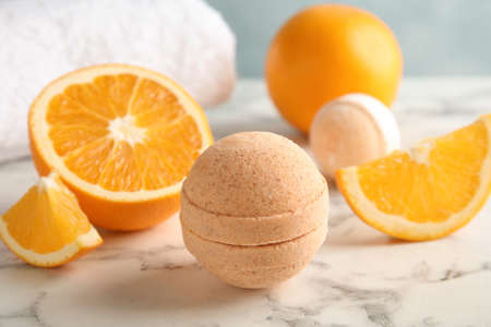 Bath bomb and orange slices on marble table