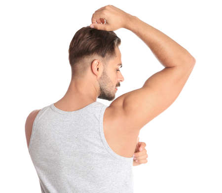 Young man showing armpit on white background. Using deodorant Stock Photo