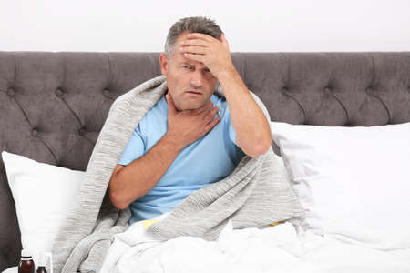 Man suffering from cough and headache in bed at home Reklamní fotografie