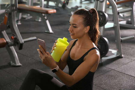 Portrait of athletic woman with protein shake and smartphone in gym Stock Photo