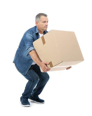 Full length portrait of mature man lifting carton box on white background. Posture concept