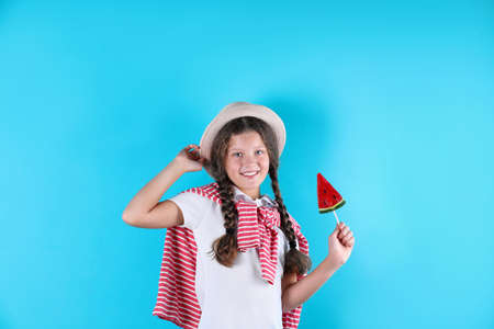 Little girl with candy on color background