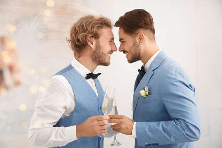 Happy newlywed gay couple with glasses of champagne at home