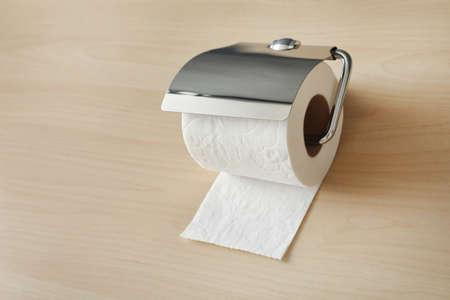 Holder with toilet paper roll on wooden background Standard-Bild