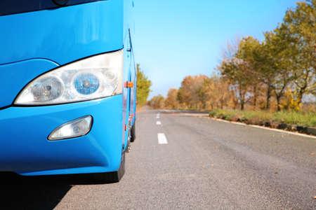 Modern blue bus on road, focus on headlight. Passenger transportation