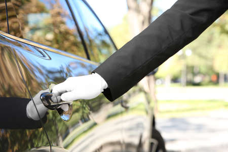 Driver opening car door, closeup. Chauffeur service