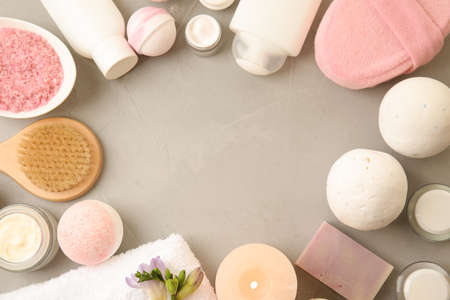 Flat lay composition with bath bombs, toiletries and space for text on grey background