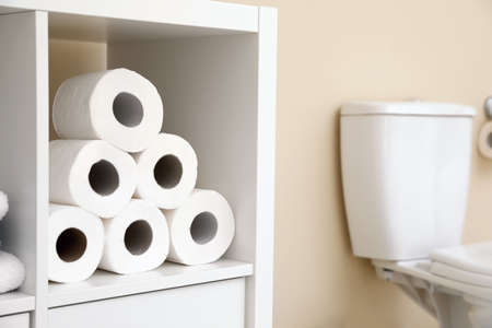Toilet paper rolls on cabinet shelf in bathroom