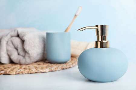Stylish soap dispenser, holder with toothbrush and towel on table. Space for text