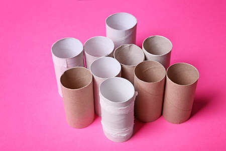 Empty toilet paper rolls on color background