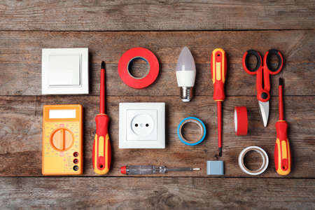 Flat lay composition with electrician's tools on wooden background