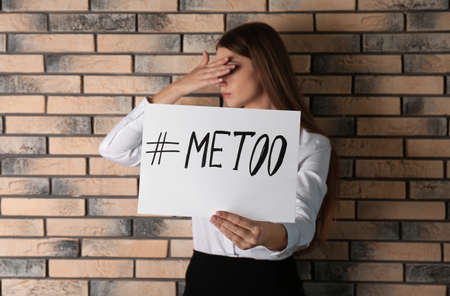 Woman holding paper with text #METOO near brick wall. Problem of sexual harassment at work