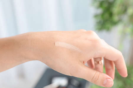 Woman testing foundation tone on hand, closeup Stock Photo