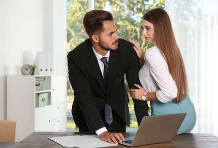 Vrouw molestert haar mannelijke collega op kantoor. Seksuele intimidatie op het werk Stockfoto