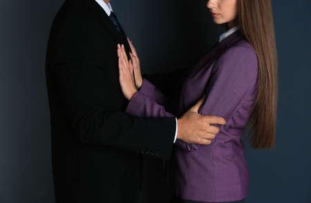 Baas molesteren zijn vrouwelijke secretaresse op donkere achtergrond, close-up. Seksuele intimidatie op het werk Stockfoto