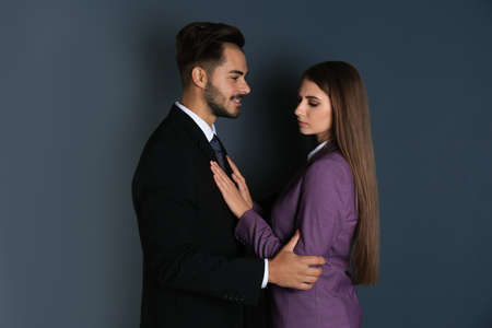 Boss molesting his female secretary on dark background. Sexual harassment at work Stock Photo