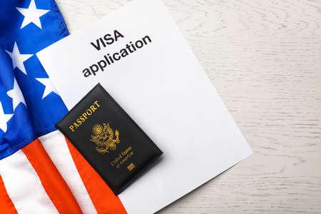 Flache Laienzusammensetzung mit Flagge der USA, Pass- und Visumantrag auf Holzhintergrund Standard-Bild
