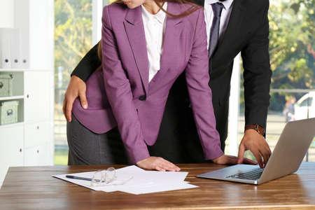 Jefe abusando sexualmente de su secretaria en la oficina. Acoso sexual en el trabajo