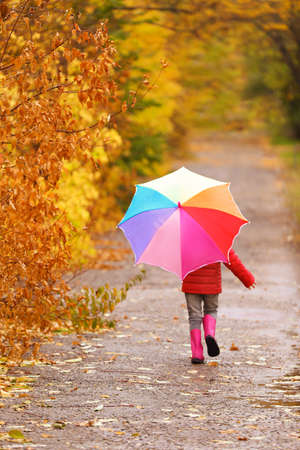 Little girl with umbrella taking walk in autumn park on rainy day Stock Photo