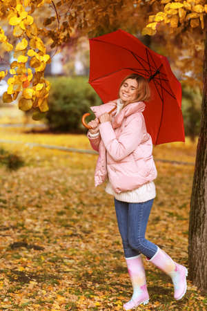 Woman with umbrella in autumn park on rainy day Stock fotó