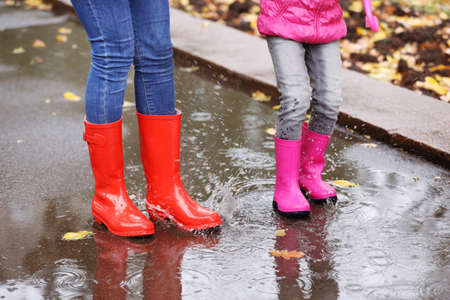 Mother and daughter wearing rubber boots splashing in puddle on rainy day, focus of legs. Autumn walk Stock Photo