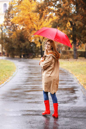 Woman with umbrella taking walk in autumn park on rainy day Stock Photo