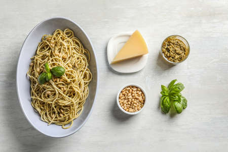 Plate of delicious basil pesto pasta with ingredients on white background, flat lay