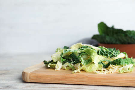Cutting board with chopped savoy cabbage on table. Space for text