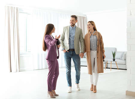 Female real estate agent showing new house to couple, indoors Banco de Imagens